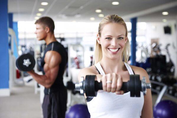 Beautiful young woman smiles at the camera while lifting weights at the gym. Horizontal shot.