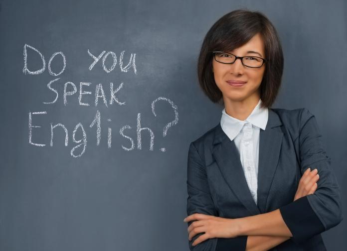 Teacher is standing near blackboard