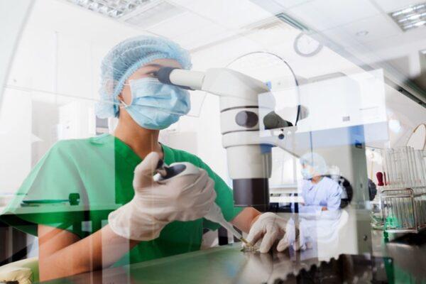 Asian scientist using microscope in the laboratory