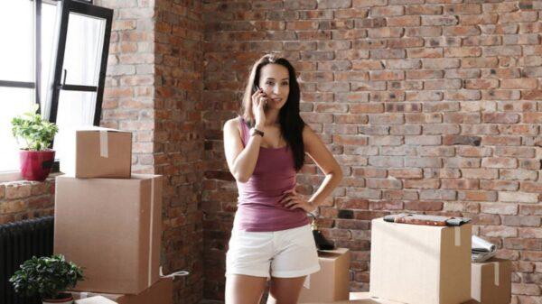 mulher-jovem-fala-ao-telefone-entre-caixas-na-casa-nova